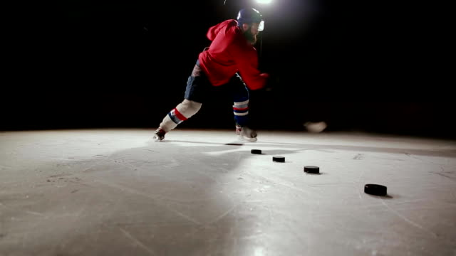 professional hockey player produces a shot on goal at ice arena - praticare video stock e b–roll
