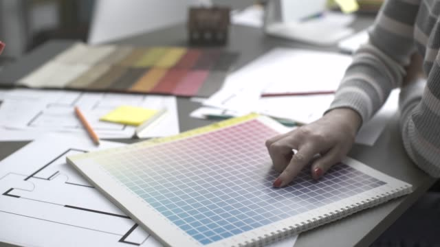 Professional interior designer working on a project Professional interior designer working on a project, she is picking color swatches and drawing on a house plan fabric swatch stock videos & royalty-free footage