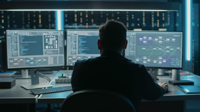 Video Professional IT Programer Working in Data Center on Desktop Computer with Three Displays, Doing Development of Software and Hardware. Displays Show Blockchain, Data Network Architecture. Back View