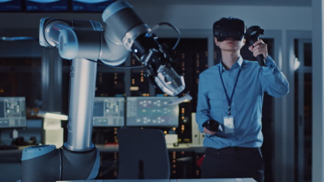 Professional Japanese Development Engineer in Blue Shirt is Controlling a Futuristic Robotic Arm with a Augmented Reality Headset and Joysticks in a High Tech Research Laboratory with Modern Equipment.
