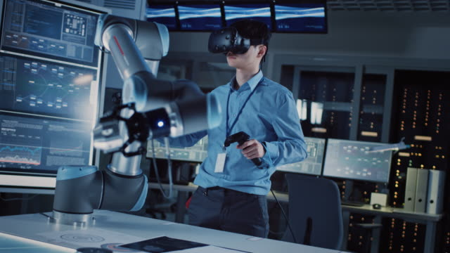 vídeos de stock e filmes b-roll de professional japanese development engineer in blue shirt is controlling a futuristic robotic arm with a virtual reality headset and joysticks in a high tech research laboratory with modern equipment. - man joystick