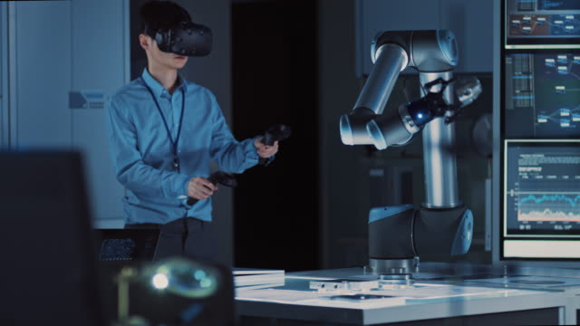 Professional Japanese Development Engineer in Blue Shirt is Controlling a Futuristic Robotic Arm with a Virtual Reality Headset and Joysticks in a High Tech Research Laboratory with Modern Equipment. Professional Japanese Development Engineer in Blue Shirt is Controlling a Futuristic Robotic Arm with a Virtual Reality Headset and Joysticks in a High Tech Research Laboratory with Modern Equipment. Shot on RED EPIC-W 8K Helium Cinema Camera. robot stock videos & royalty-free footage