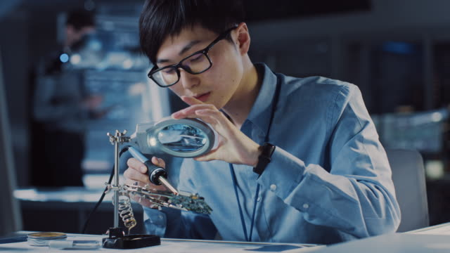 professional japanese electronics development engineer in blue shirt is soldering a circuit board in a high tech research laboratory with modern computer equipment. - apprendista video stock e b–roll
