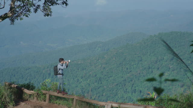 Professional landscape photographer taking photos at nature mountain view video