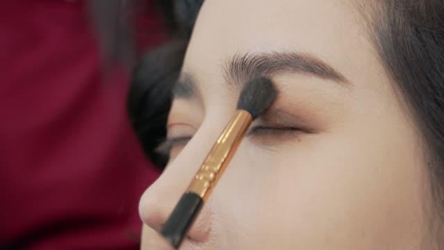 プロのメイクアップとクローズアップショットに彼女の目の近くに化粧ブラシ - アイシャドウ点の映像素材/bロール