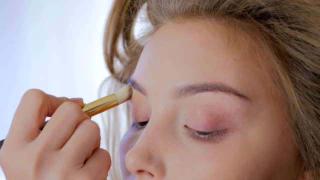 Professional make-up artist applying cream base eyeshadow primer to model eye video