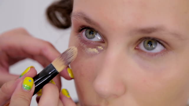 Professional make-up artist applying cream base eyeshadow primer to model eye Professional make-up artist applying cream base eyeshadow primer to model eye. Beauty, makeup and fashion concept foundation make up stock videos & royalty-free footage