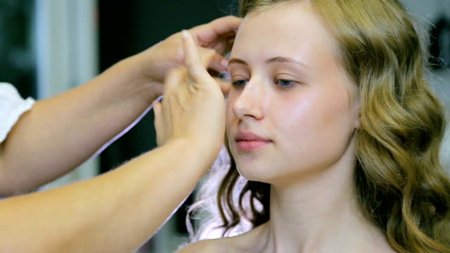 Professional make-up artist applying cream base to blond long curl hair and blue eyes model skin video