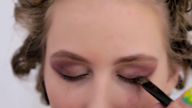 stockvideo's en b-roll-footage met professionele make-up artiest toepassing van oogschaduw - ooglid