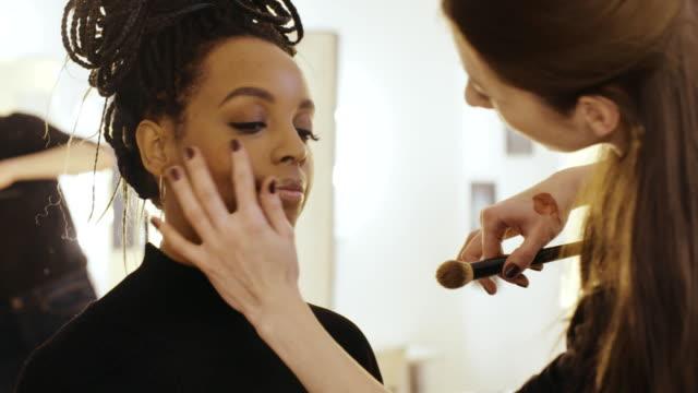 professionell makeupartist tillämpa flytande highlighter för glänsande kindben - makeup artist bildbanksvideor och videomaterial från bakom kulisserna
