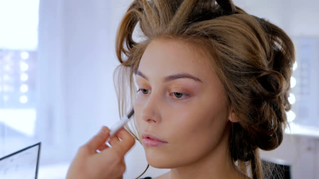 Professional make-up artist applying makeup on woman's face video
