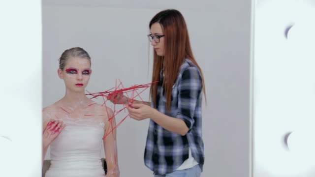 Professional make-up artist finishing halloween style for teen girl video