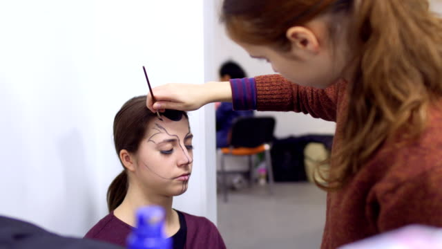 stockvideo's en b-roll-footage met professionele visagist maakt greasepaint voor jonge actrice in kleedkamer - vetschmink
