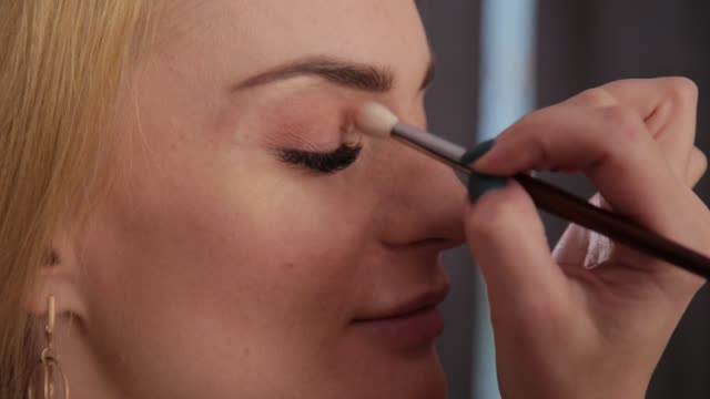 Professional makeup artist makes makeup a very beautiful woman Professional makeup artist makes makeup a very beautiful woman eyeshadow stock videos & royalty-free footage