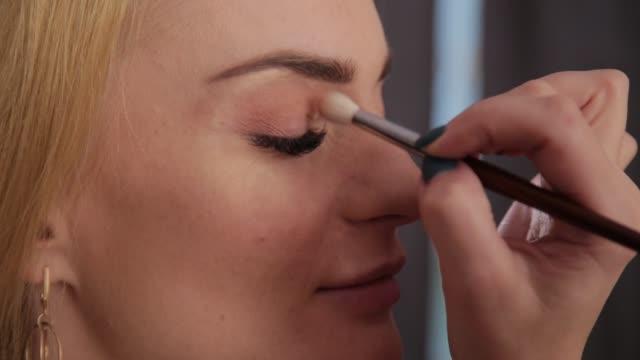 vidéos et rushes de l'artiste de maquillage professionnel fait le maquillage une femme très belle - fard à paupières