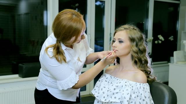 vidéos et rushes de maquilleuse professionnelle rend maquillage lèvres de la jeune femme avec le crayon à lèvres. - crayon à lèvres