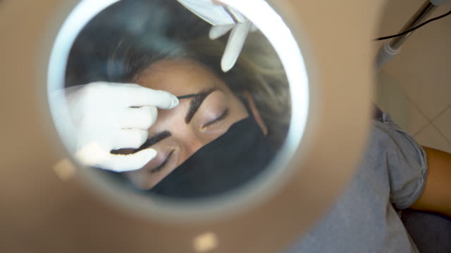 Professional makeup artist paints eyebrows to client video