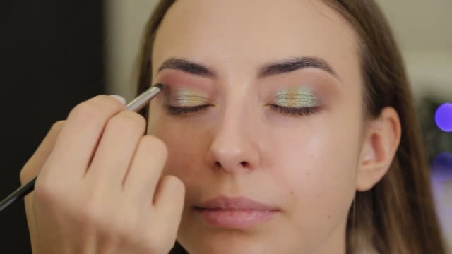 Professional makeup artist puts eye shadow on a client of a beauty salon