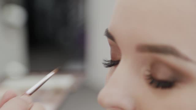 プロのメイクアップアーティストの女性は、パレット上のメイクアップクリームをかき混ぜる - アイシャドウ点の映像素材/bロール