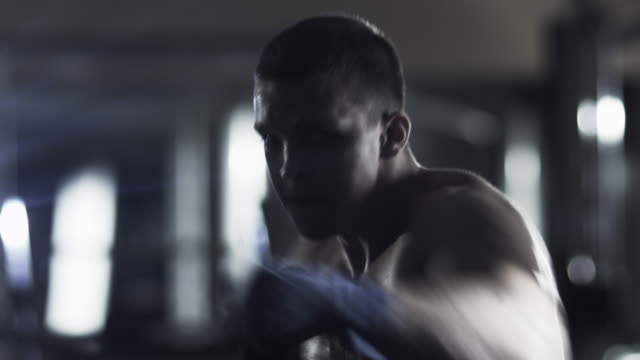 Professional male boxer is training punches and kicks in dark gym.
