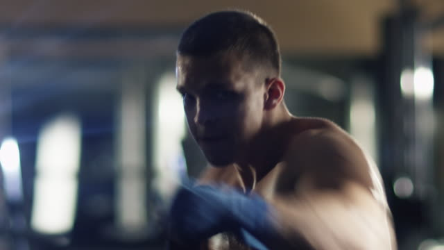 Professional male boxer is training punches and kicks in the gym.