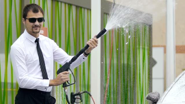 professionell manlig business class förare rengöring auto på självbetjäning biltvätt - surf garage bildbanksvideor och videomaterial från bakom kulisserna