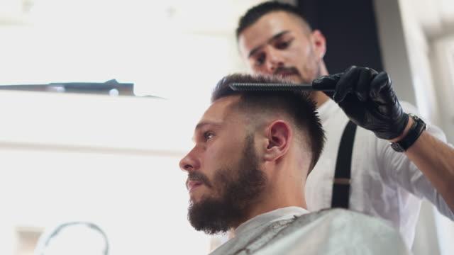 ヘアカットを与えるプロの男性美容師 - 美容院点の映像素材/bロール