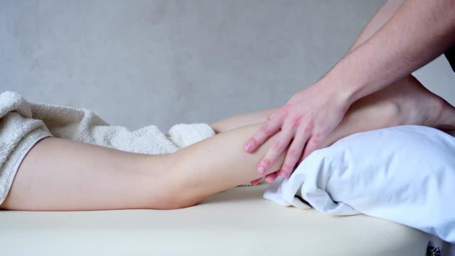 professionell manlig massör knådar ben av flicka patient, som ligger på soffan i ljusa kontor - massageterapeut bildbanksvideor och videomaterial från bakom kulisserna