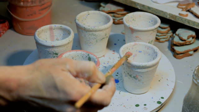 Professional male potter painting mugs in pottery workshop Professional male potter painting mugs in pottery workshop, studio. Crafting, artwork and handmade concept painting art product stock videos & royalty-free footage