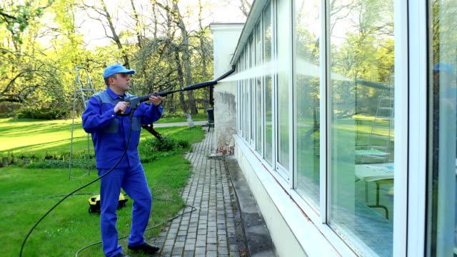 uomo professionista pulizia finestre sporche con getto d'acqua ad alta pressione - tubo flessibile video stock e b–roll