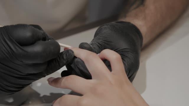 vidéos et rushes de l'homme manucure professionnel soulève des cuticules pour l'outil spécial d'udvivaniya plus loin - cuticule