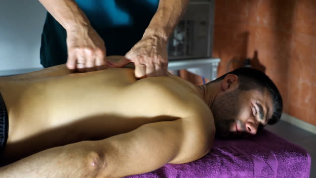 Professional massagist doing health rubdown of back to athlete in parlor. Muscular sportsman lying on massage table and male hands of masseur slowly massaging him shoulders in salon. Side view Slow motion