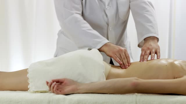 Professional masseur doing back massage young girls in a massage parlor video