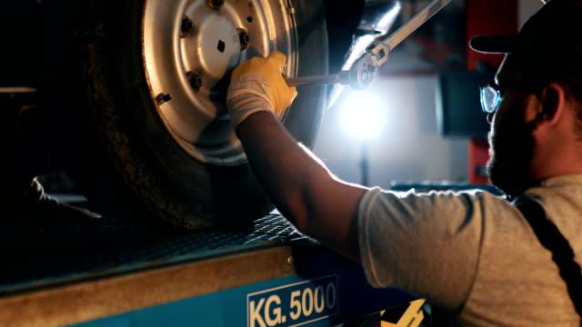 Professional mechanic in uniform repairing car in workshop