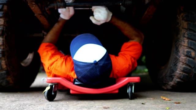 professional mechanic in uniform repairing car in workshop - truck tire video stock e b–roll