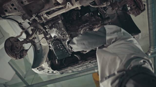 vídeos de stock e filmes b-roll de professional mechanic repairing a car in auto repair shop - instrumento para diagnóstico