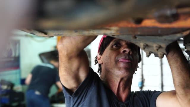 stockvideo's en b-roll-footage met professionele werktuigkundige herstellen van een auto in auto reparatiewerkplaats - vuil