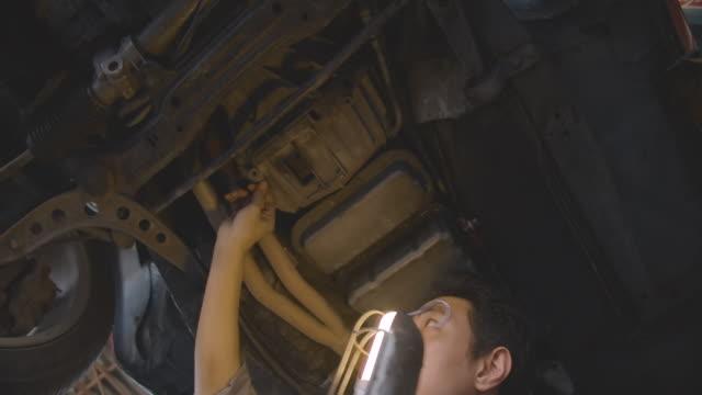Professional men mechanic working under lifted car at auto repair shop, car service concept.