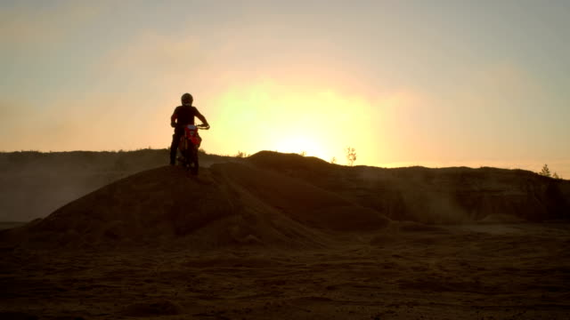 professional motocross biker spectacularly stands on the off-road dune on his enduro motorcycle. - freestyle motocross video stock e b–roll
