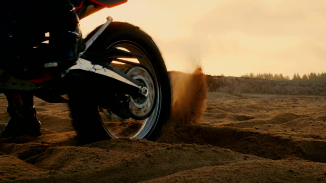 professional motocross motorcycle rider drives on the off-road sand terrain. shot on the scenic quarry with setting sun. - motocross video stock e b–roll
