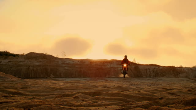 professional motocross motorcycle rider drives over the dune and further down the off-road track. it's sunset and track is covered with smoke/ mist. - freestyle motocross video stock e b–roll