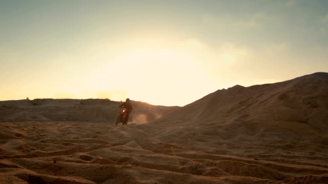 professional motocross motorcycle rider driving over the dune and further down the off-road track. it's sunset and track is covered with smoke/ mist. - freestyle motocross video stock e b–roll
