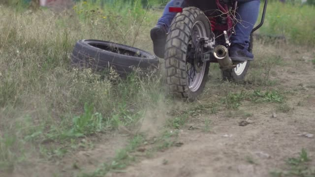 professional motorcyclist drift and turns on a motorcycle on the ground, a biker does a trick on a motorcycle. slow motion - freestyle motocross video stock e b–roll