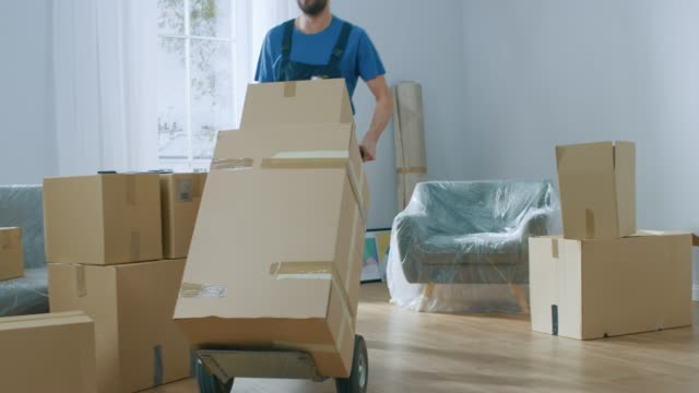 professional mover with hand truck loads it with cardboard boxes and helps people move out and relocate into the new house. - new home stock videos & royalty-free footage