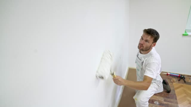 Professional painter painting the wall white using a painting roller Professional painter at work. Painter painting the walls with a painters roller and brush for more precise application. Construction worker painting the walls with white wall paint. Room makeover in progress. house painter stock videos & royalty-free footage