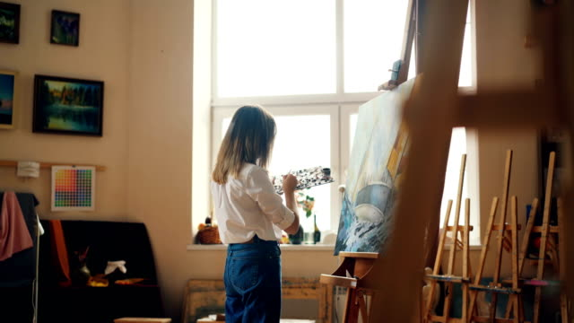 professional painter young lady is painting seascape with acrylic paints depicting marine landscape ship and sea waves working alone in studio. people and work concept. - pittore video stock e b–roll