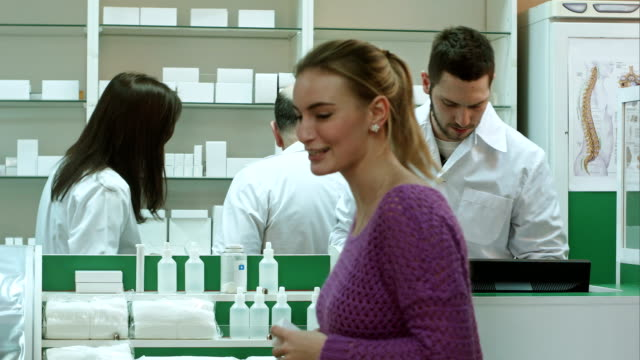 Professional pharmacist and pharmacy technician working in drugstore video