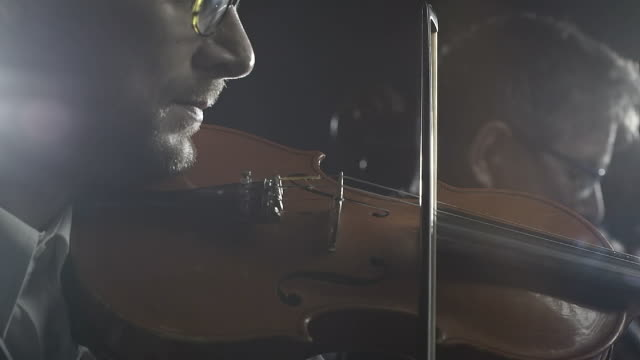 Professional philharmonic orchestra playing together on stage Professional philharmonic orchestra playing on stage, a cellist and a violinist are performing together classical concert stock videos & royalty-free footage