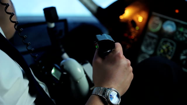 Professional pilot coordinating flight details, talking on radio to controller video