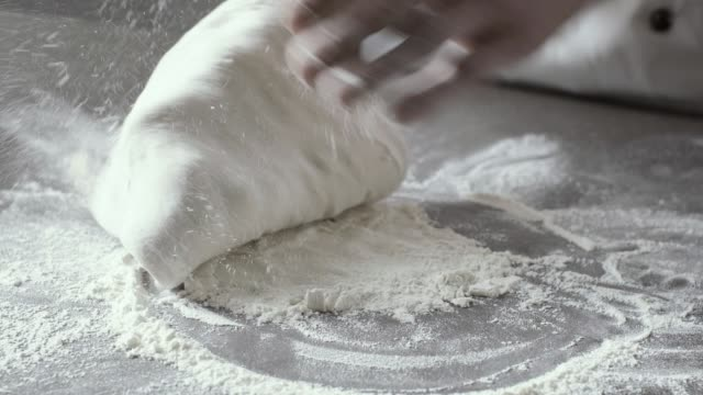 Professional pizza maker stretching the dough Professional pizza maker stretching and dusting the dough with flour on the kitchen worktop dough stock videos & royalty-free footage